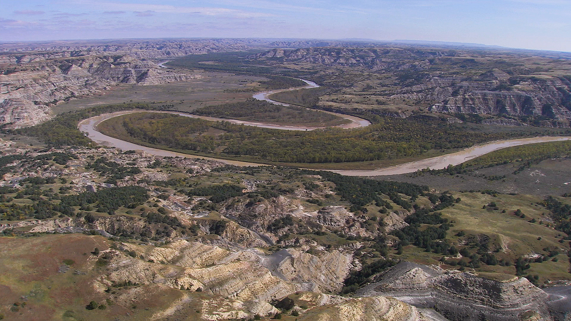 aerial of river running through theodore roosevelt national park
